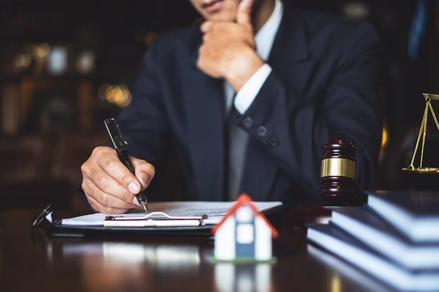 コンサルタント弁護士の概念のための仕事場で契約書を書くまたは読む弁護士実業家を閉じる。 Premium写真
