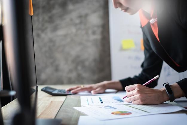 ビジネスの女性のための計算機とラップトップを使用してオフィスで木製の机の上の数学の金融を閉じる Premium写真