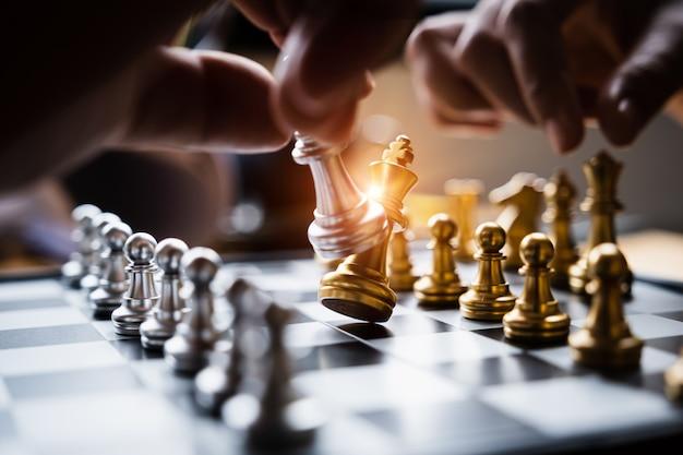Бизнесмен играя или двигая диаграмму шахмат в игре успеха конкуренции. Premium Фотографии
