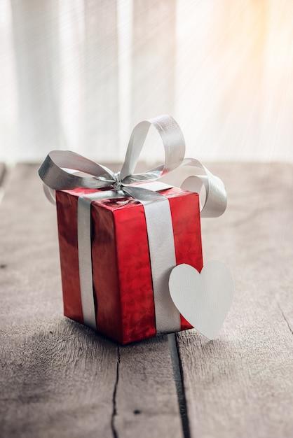 赤いギフトボックスと白い木製のテーブル上の心 Premium写真