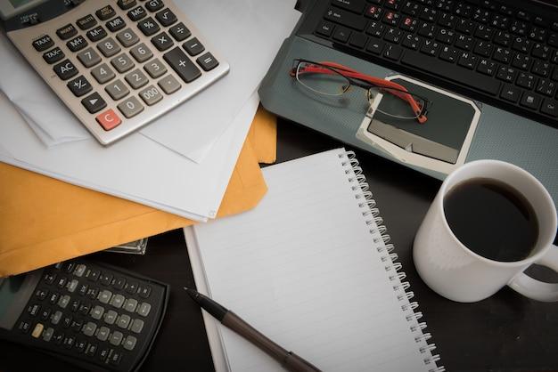 コーヒーカップ、ラップトップ、ドキュメントファイル、ペン、電卓、メモ帳、木製テーブルの上のグラス Premium写真