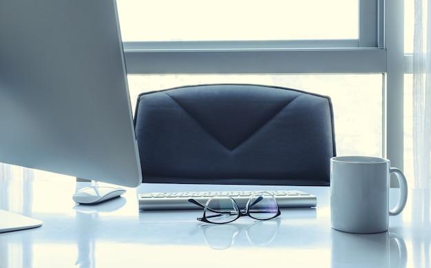 デスクトップコンピューターと眼鏡のマネージャーテーブル Premium写真
