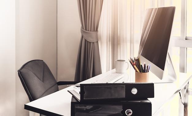 デスクトップコンピュータとビジネスノートを含むマネージャテーブル Premium写真