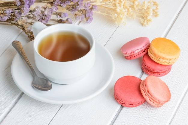 熱いお茶のカップとマカロンの種類の色 Premium写真