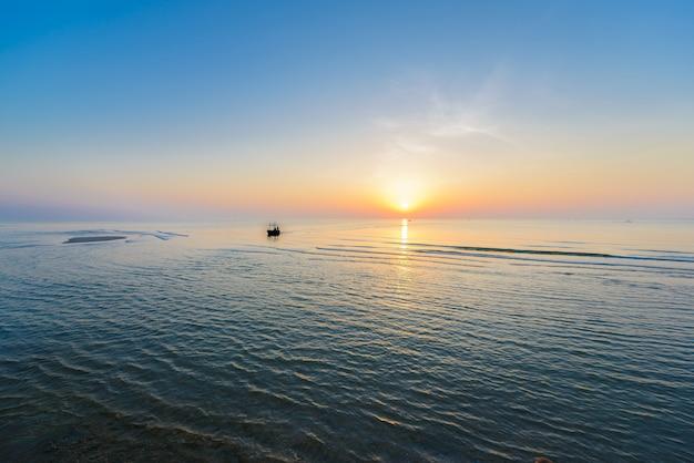 ビーチで美しい熱帯の日の出。 Premium写真