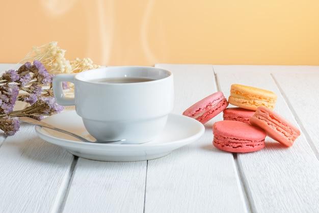 白い木の表面に熱いお茶のカップとマカロンの種類の色 Premium写真