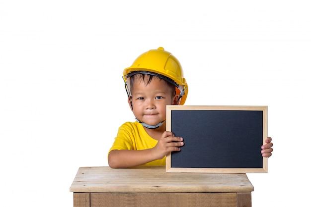 アジアの子供たちが安全ヘルメットを着用し、白い背景で隔離の黒板に笑みを浮かべて。子供と教育の概念 Premium写真