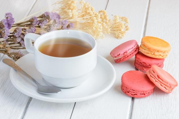 一杯の熱いお茶とマカロンのさまざまな種類の色 Premium写真