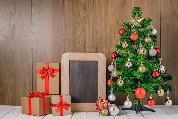 Елка с разноцветными шариками, украшения и подарочные коробки с классной доской Premium Фотографии