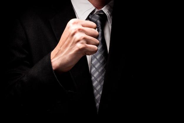 黒の背景に手ジェスチャーで黒のスーツの男の近く。 Premium写真