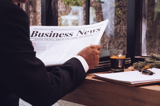 ビジネスマン、カフェで新聞を読んでいる Premium写真