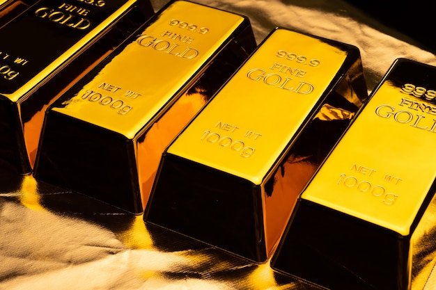 Золотые слитки на блестящей желтом фоне. Premium Фотографии