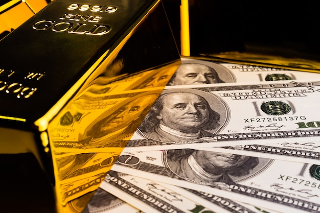 Закройте вверх золотых слитков и банкнот. финансовая концепция Premium Фотографии