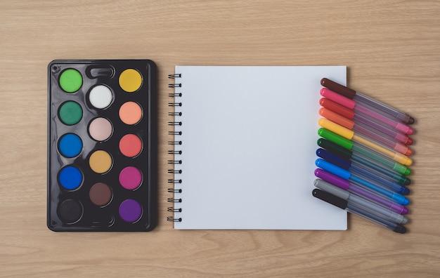 多くのカラフルなペンと茶色の木製テーブルに水彩パレットのメモ帳またはノートブック。 Premium写真