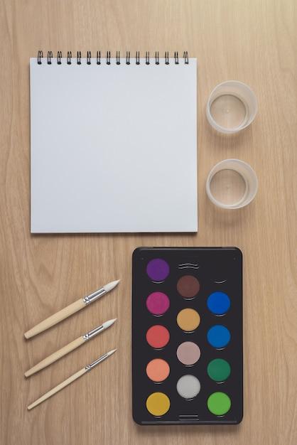 多くのカラフルなペン、ペイントブラシ、茶色の木製テーブルの水彩パレットのメモ帳またはノートブック。 Premium写真