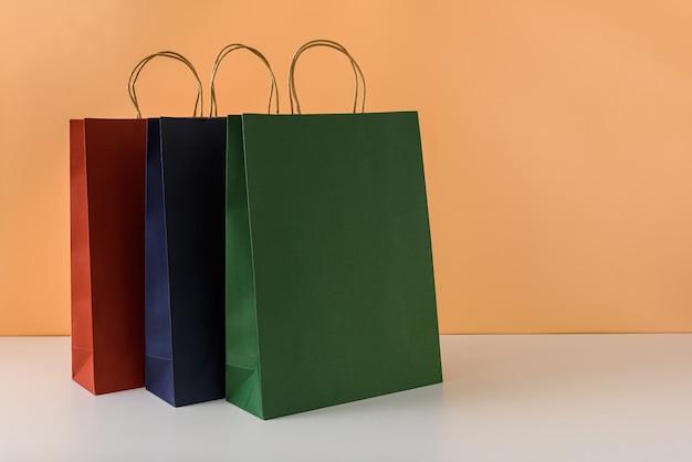 空白のクラフトパッケージまたはハンドル付きのカラフルな紙の買い物袋のモックアップ Premium写真