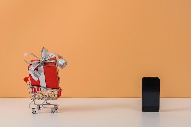赤いリボンの弓とショッピングカートまたは白いテーブルとパステルオレンジの壁にトロリーの多くのギフトボックス Premium写真