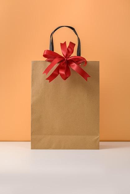 赤いリボンの弓とハンドルが付いたクラフトパッケージまたは茶色の紙のショッピングバッグ。 Premium写真