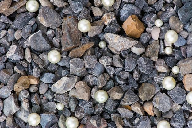 コンクリートの石の背景、小石の白い真珠の女性のエンパワーメントとコンクリートの石のクローズアップ Premium写真