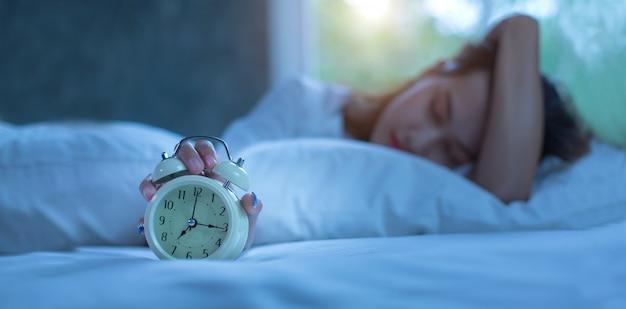 夜アラーム付きベッドで寝ている若い女性 Premium写真