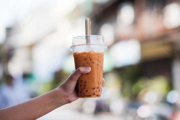 ぼかしの背景を持つ台湾アイスバブルミルクティーのプラスチックガラスを持っている手、 Premium写真
