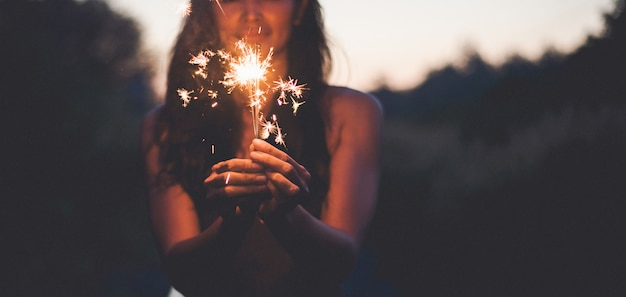 抽象的なぼかし花火のお祝い、モーションによって風がぼやけている女性の手が自然とツイルライトの空に燃えるクリスマスの輝きを持つ Premium写真