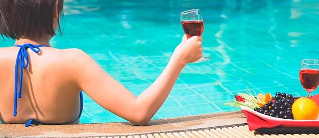 幸せな女の子が遊んで、夏休みの間にプールでリラックス Premium写真