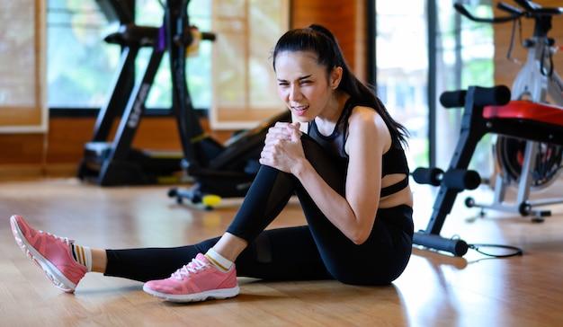 運動から負傷した若い女性。ジムで膝の痛みを持つフィット女性 Premium写真