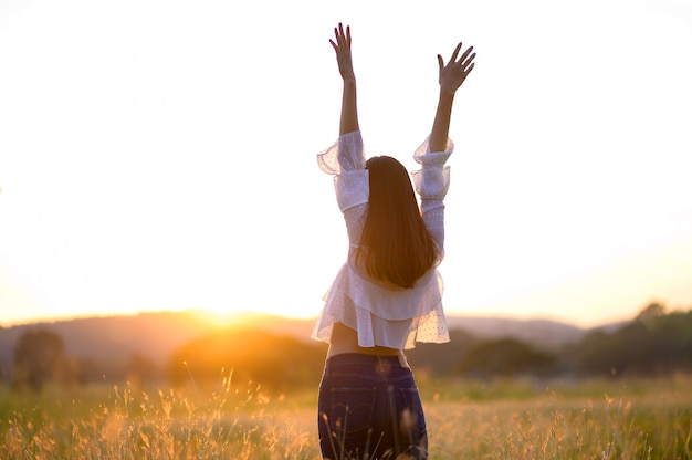 Девушка, наслаждаясь природой на поле. солнечный свет. свечение солнца. свободная счастливая женщина Premium Фотографии
