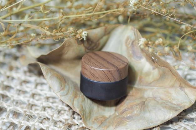 化粧品ボトルは茶色の製品に織りハンドバッグを入れています。 Premium写真