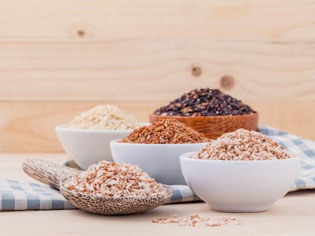 Цельнозерновой рис для здоровой и чистой пищи на деревянном фоне. Premium Фотографии