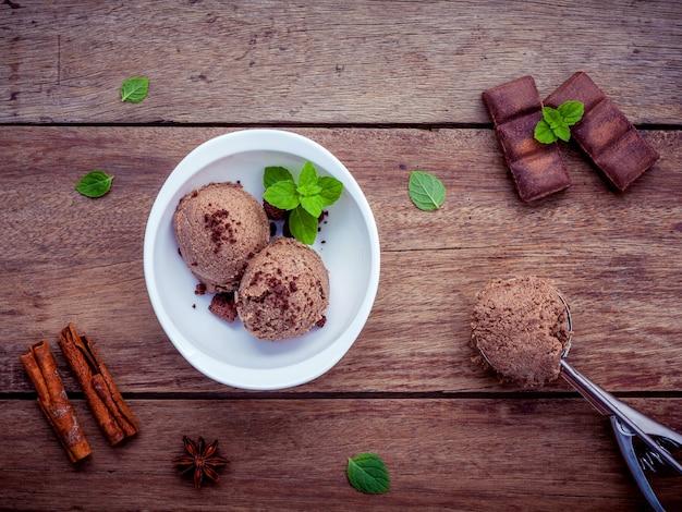 木製の背景に新鮮なペパーミントの葉のセットと白いボウルのチョコレートアイスクリーム。 Premium写真