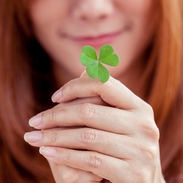 女の子はクローバーの葉を握る Premium写真