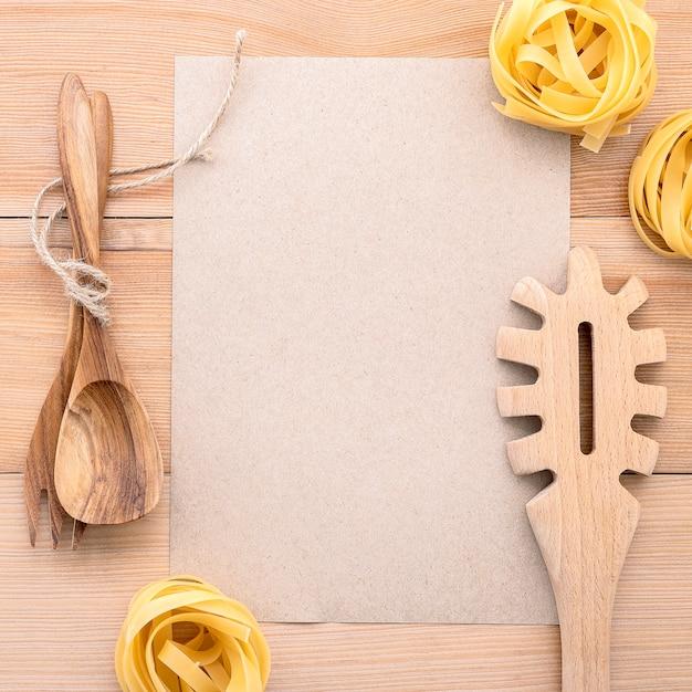 イタリア料理のコンセプトとメニュー空白の紙と木のパスタお玉。 Premium写真