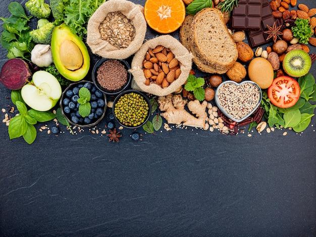 健康食品の選択のための成分。健康食品の概念は、暗い石の背景に設定します。 Premium写真