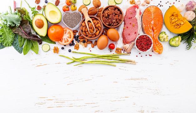 白い木製の背景に健康食品の選択のための原料。 Premium写真