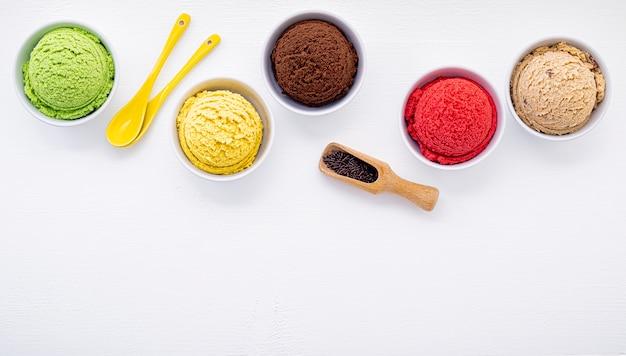 白い木製の背景にさまざまなアイスクリーム味のボールを設定します。 Premium写真