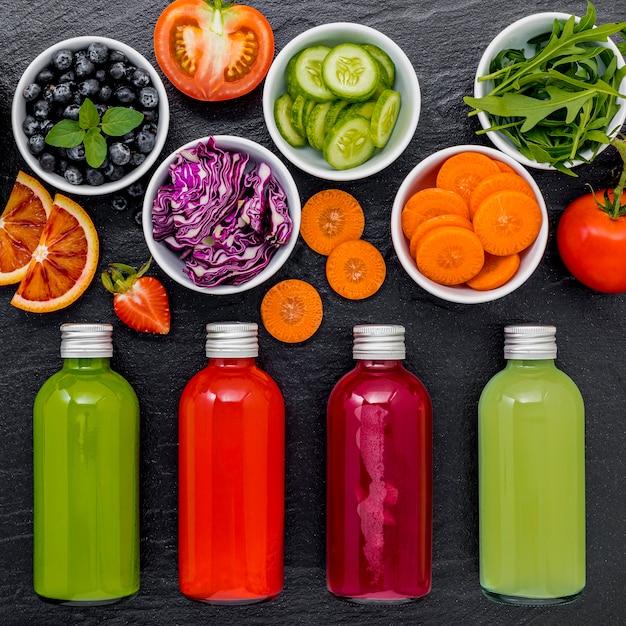 カラフルな健康的なスムージーと新鮮なトロピカルフルーツとコピースペースを持つ暗い石の背景にスーパーフードの瓶の中のジュース。 Premium写真