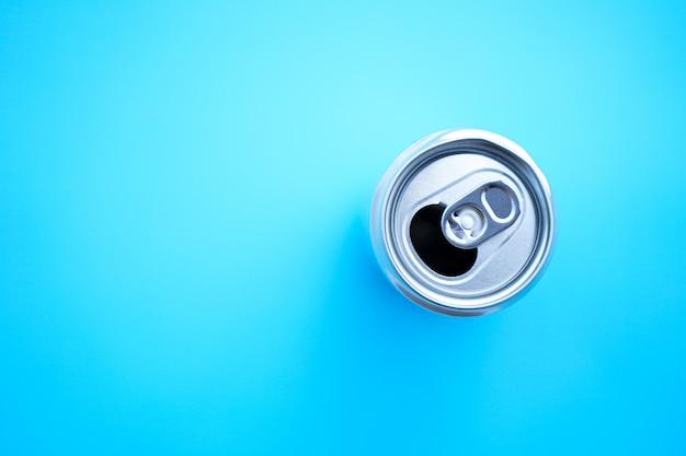 Плоская кладка алюминиевой банки открыта на синем фоне Premium Фотографии
