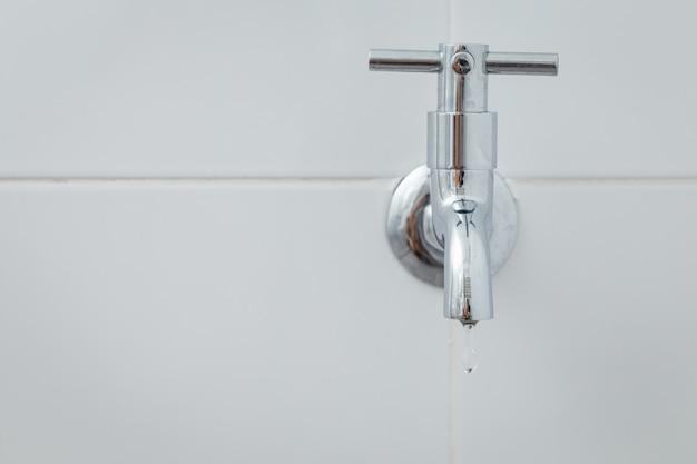 白いタイル張りの床に銀の金属蛇口 Premium写真