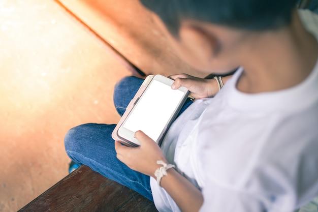 Молодой азиатский мальчик сидя на деревянном стуле играя мобильные телефоны вне дома Premium Фотографии