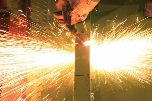 金属トーチを使用して鋼棒を切断する労働者 Premium写真