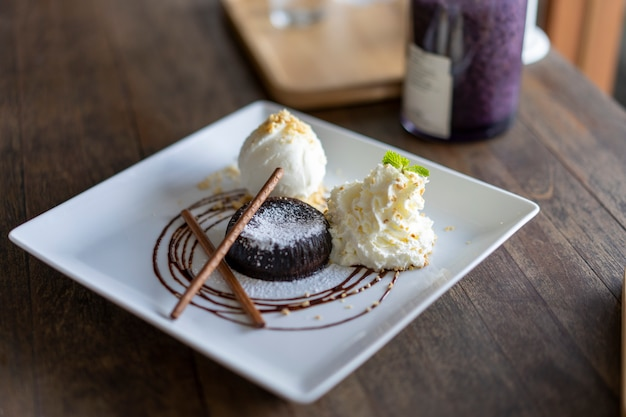 Шоколадный торт и ванильное мороженое красиво уложены на тарелку. Premium Фотографии