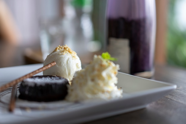 チョコレートケーキとバニラアイスクリームは美しく皿の上に置かれます。 Premium写真