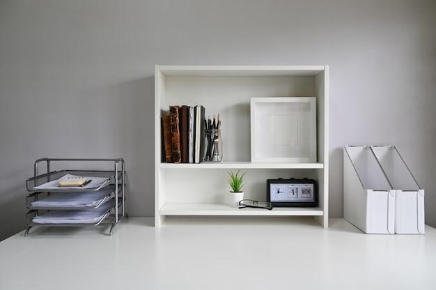 テーブルの上の棚とオフィス用品のあるワークスペース。 Premium写真