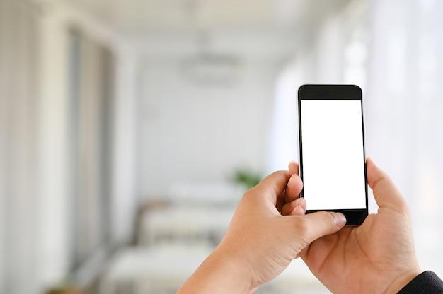Руки человека используя мобильный телефон модель-макета с пустым экраном в живущей комнате. Premium Фотографии