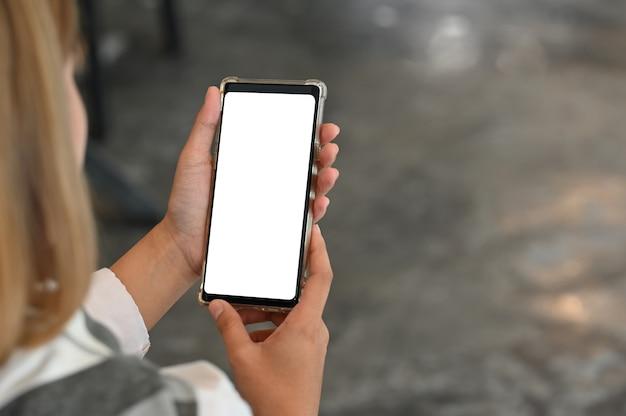 Молодая женщина, используя смартфон с пустой экран. Premium Фотографии