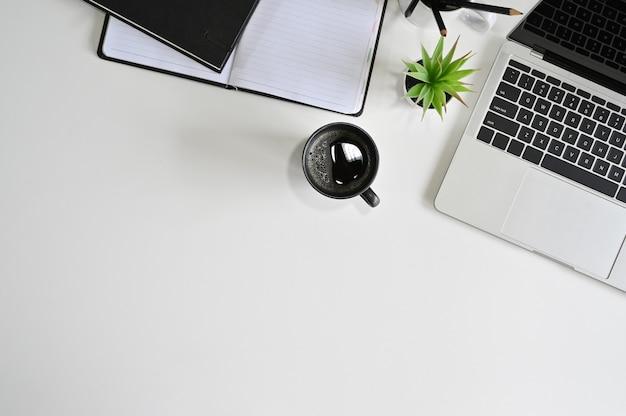 トップビューオフィスデスクラップトップコンピューター、コーヒー、白いテーブルに鉛筆とノート。 Premium写真