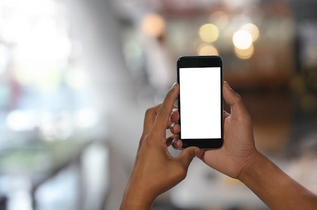 部屋の背景のボケ味でモックアップのスマートフォンを使用してショット男の手をトリミングしました。 Premium写真