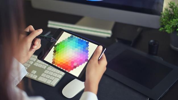 Молодой женский творческий художник веб-дизайна с работой над выбором цвета на графической таблетке. Premium Фотографии